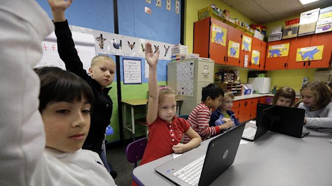 In this photo taken Nov. 4, 2015, kindergartner Lauren Meek, second left, raises her hand as she sits with second grade students helping her on programming during their weekly computer science lesson at Marshall Elementary School in Marysville, Wash. The school, north of Seattle, joined a growing movement nationwide to expose more public school children to computer science, even as early as in kindergarten. (AP Photo/Elaine Thompson)