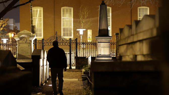 In this Jan. 15, 2013 photo, Jeff Jerome walks in a cemetery that is home to Edgar Allan Poe's grave in Baltimore. For years, Jerome watched as a mysterious man known as the Poe Toaster left three roses and an unfinished bottle of cognac at Poe's grave every year on the legendary writer's birthday. His identity is a great modern mystery, and just as mysteriously, the tradition ended four years ago. (AP Photo/Patrick Semansky)