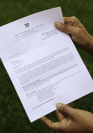 In this May 31, 2013, photo, breast cancer survivor Alicia Cook holds a letter from the University of Chicago informing her that test results showed she had the BRCA genetic defect linked to breast cancer, outside her home in Chicago. New research shows genetic breast cancer is more common in black women than previously thought. (AP Photo/M. Spencer Green)
