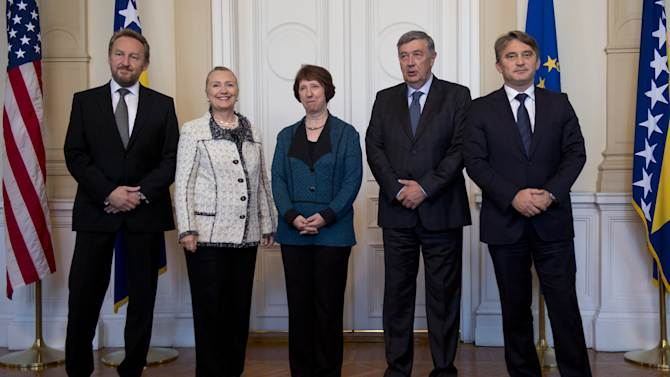 CORRECTS LOCATION FROM US EMBASSY TO PRESIDENCY US Secretary of State Hillary Rodham Clinton, second left, with High Representative for EU Foreign Policy Catherine Ashton, centre, stand alongside Chairman Bakir Izetbegovic, left, Members of the Bosnia and Herzegovina Tri-Presidency, Nebojsa Radmanovic, second right and  Zeljko Komsic, right, prior to meetings at the Presidency, in Sarajevo, Bosnia, Tuesday, Oct. 30, 2012. The top American and European diplomats are on a joint diplomatic tour of the Balkans, urging rival ethnic groups and governments in Bosnia, Serbia and Kosovo to settle their differences for the good of their nations. U.S. Secretary of State Hillary Rodham Clinton was talking Tuesday with European Union foreign policy chief Catherine Ashton in the Bosnian capital of Sarajevo. They are then meeting together with Bosnia's three presidents before travelling to Belgrade for similar talks with Serbian leaders. Clinton and Ashton will see Kosovo's leaders on Wednesday. (AP Photo/Saul Loeb, Pool)