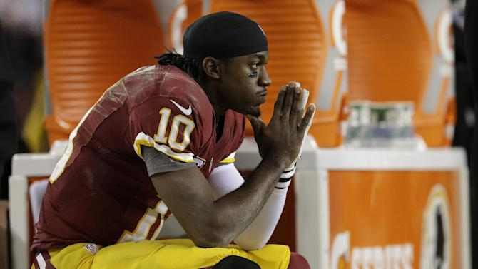 Washington Redskins quarterback Robert Griffin III sits on the bench after a knee injury during an NFL wild card playoff football game against the Seattle Seahawks in Landover, Md., Sunday, Jan. 6, 2013. The Seahawks defeated the Redskins 24-14. (AP Photo/Evan Vucci)