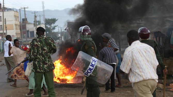 Police extinguish fire set by Raila Odinga's supporters in Kondele, Kisumu Saturday, March 30, 2013 after the Supreme Court declared President elect Uhuru Kenyatta as the fourth president of the Republic of Kenya.(AP Photo/James Kaii)