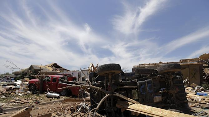 Vehicles destroyed by Monday's tornado sit on the front lawns of homes as area residents begin clean up efforts Wednesday, May 22, 2013, in Moore, Oklahoma. (AP Photo/Tony Gutierrez)