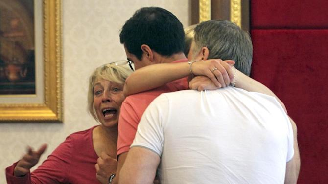 Family members of Hannah Witheridge,  one of two slain British tourists,  hug each other at the Royal Thai Police Headquarters before meeting with Thai police in Bangkok, Thailand, Thursday, Sept. 18, 2014. Police in Thailand said Wednesday that DNA samples from the bodies of two British tourists found bludgeoned on a resort island did not match any collected from 12 people who were among those in the area.(AP Photo/Sakchai Lalit)