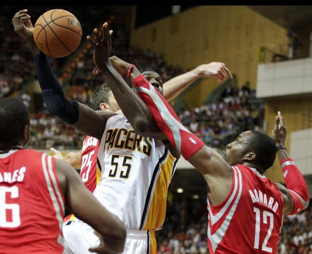 Indiana Pacers' Roy Hibbert is fouled by Houston Rockets' Dwight Howard in the first quarter of their NBA pre-season basketball game in Taipei Arena