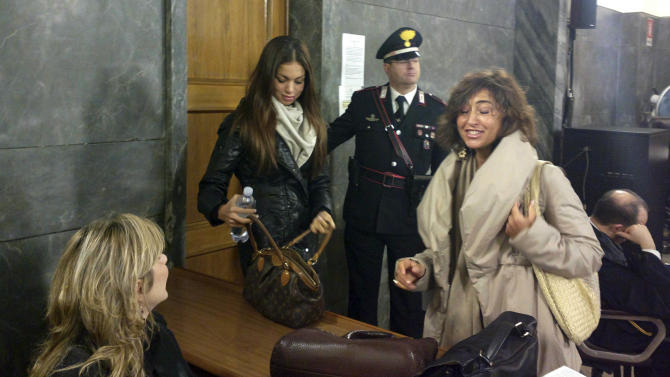 Karima el-Mahroug, left, the Moroccan woman at the center of ex-Premier Silvio Berlusconi's sex-for-hire trial, arrives in a court room to testify as a witness for the first time, in Milan, Monday, Jan. 14, 2013. El-Mahroug was ordered by the court to appear Monday to testify after failing to show on two previous dates because she was reportedly in Mexico on vacation. She has been called as a defense witness. Berlusconi is accused of paying for sex with woman, better known as Ruby, when she was 17, and then trying to cover it up. Both deny sexual contact. (AP Photo/Luca Bruno)