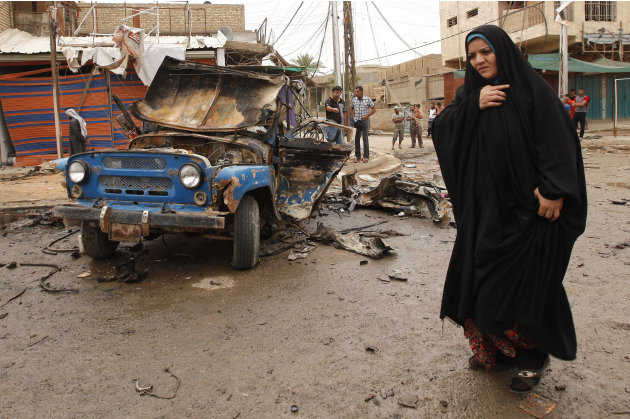 An Iraqi woman passes by the scene of a car bomb attack in Kamaliyah neighborhood, a predominantly Shiite area of eastern Baghdad, Iraq, Monday, May 20, 2013. A wave of car bombings across Baghdad's S