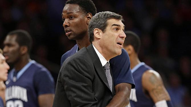Villanova's JayVaughn Pinkston restrains head coach Jay Wright during a timeout in the first half of an NCAA college basketball game against Louisville at the Big East Conference tournament, Thursday, March 14, 2013, in New York. (AP Photo/Frank Franklin II)