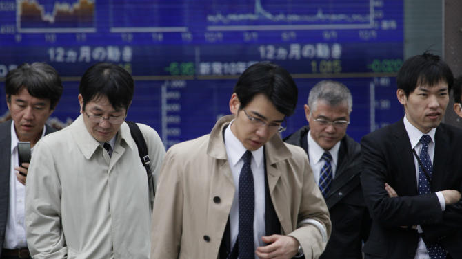 In this Dec. 9, 2011 photo, Japanese businessmen cross a traffic intersection at downtown Tokyo. A key central bank survey showed Thursday, Dec. 15 that confidence at major Japanese manufacturers fell over the last quarter, as the export-reliant country battled a strong yen and an increasingly precarious global economy. (AP Photo/Koji Sasahara)