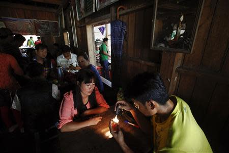 "Traders inspect jade on so-called ""jade tables"" in a tea shop in Lone Khin village, in Hpakant township, Kachin State"