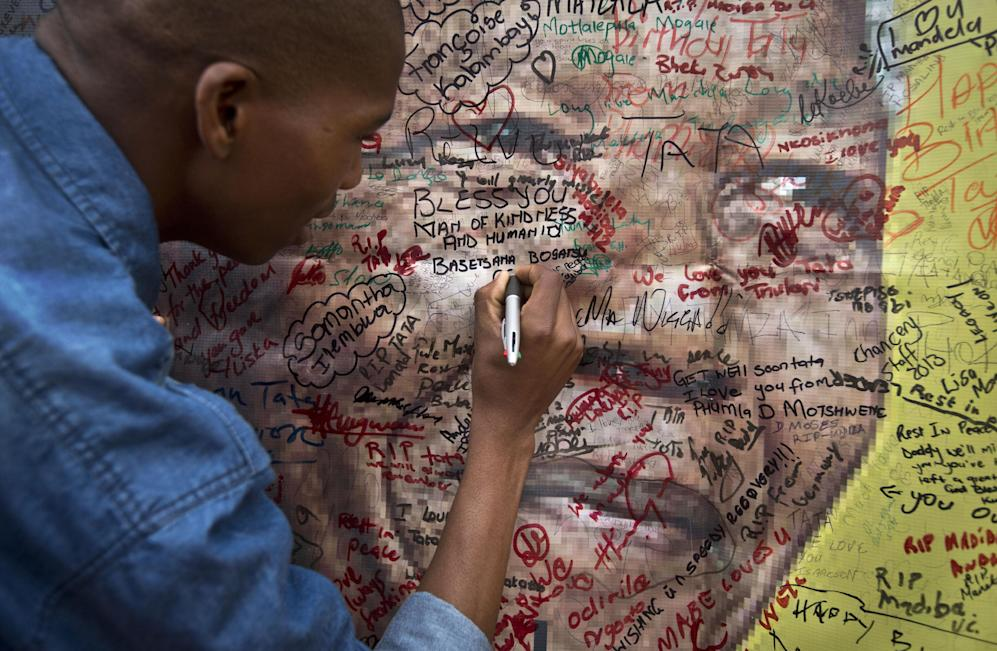 A well-wisher writes a message on a poster of Nelson Mandela on which he and others have written their messages of condolence and support, in the street outside his old house in Soweto, Johannesburg, South Africa Friday, Dec. 6, 2013. Flags were lowered to half-staff and people in black townships, in upscale mostly white suburbs and in South Africa's vast rural grasslands commemorated Nelson Mandela with song, tears and prayers on Friday while pledging to adhere to the values of unity and democracy that he embodied. (AP Photo/Ben Curtis)