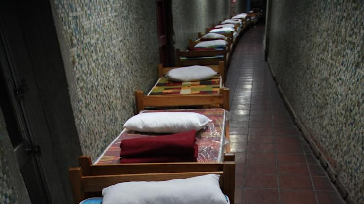 In this May 24, 2013 photo, beds line a hallway in the indoor stadium Estadio Victor Jara that opens its doors to the homeless in the evenings during the winter season in Santiago, Chile. Just around the bend is the locker room where famous Chilean folk singer Victor Jara was tortured and killed just days after the bloody military coup that ousted President Salvador Allende. (AP Photo/Brittany Peterson)
