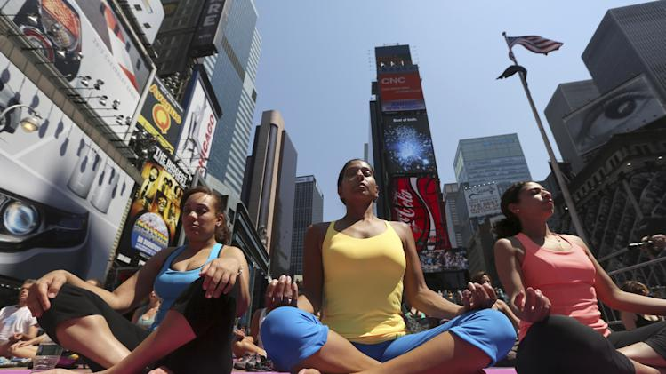 "People practice yoga in New York's Times Square, Friday, June 21, 2013. Yoga enthusiasts marked the longest day of the year with five free ""Mind Over Madness"" yoga classes in Times Square. (AP Photo/Mary Altaffer)"