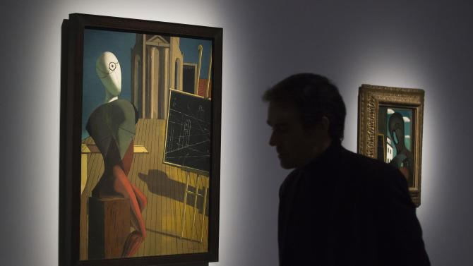 In this photo taken Tuesday, Oct. 29, 2013, a man looks at a painting entitled 'Le Prophete, 1914-1915' by Greek-born Italian artist Giorgio de Chirico, during a press day for the exhibition 'Surrealism and the object', at Pompidou Center in Paris. The exhibition at Paris' Pompidou Center tells the previously untold story of how the Surrealists managed to reconcile their fantastical dreamings and Marxist politics by channeling their artistic message through everyday objects. The exhibition runs from 30 Oct. 30, 2013 until March 3, 2014. (AP Photo/Michel Euler)
