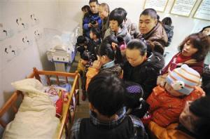 Residents visit an abandoned baby lying in a crib at a baby hatch in Guiyang