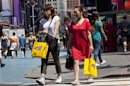 Women carry shopping bags through Times Square in New York