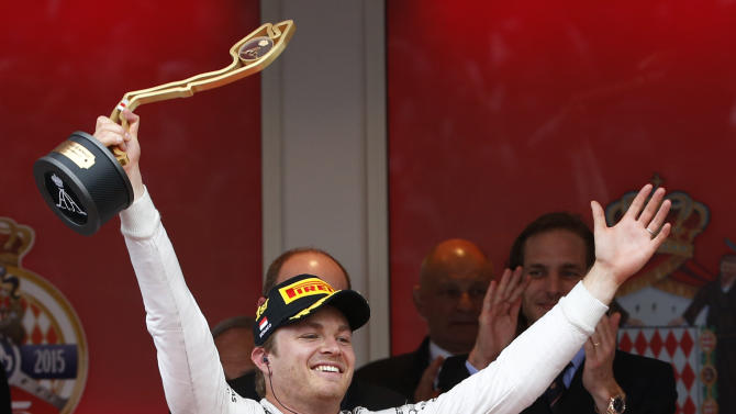 Mercedes driver Nico Rosberg of Germany holds up his trophy as he celebrates on the podium after winning the Formula One Grand Prix, at the Monaco racetrack, in Monaco, Sunday, May 24, 2015. (AP Photo/Luca Bruno)