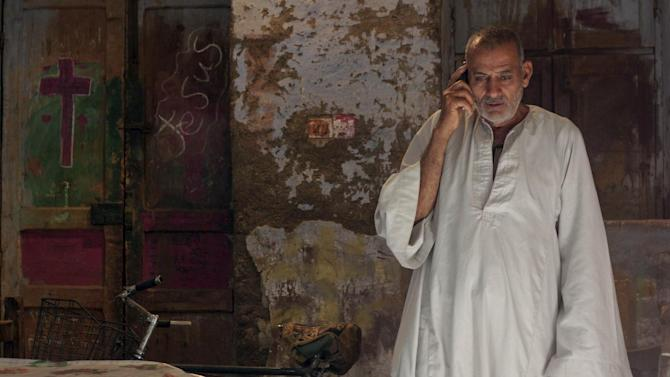 Abdel-Nour, the father of  24-year-old school teacher Dimyana Abdel-Nour, who is accused of insulting Islam while teaching fourth graders history of religions, speaks on the phone to a live television show about his daughter from his home in southern Egypt's ancient city of Luxor, Egypt, Thursday, May 16, 2013. Freed on Tuesday on a 20,000-pound (nearly 3,000 dollars) bail after nearly a week in detention, Abdel-Nour is due to stand trial later this month. Criminalizing blasphemy was enshrined in the country's new Islamist-backed constitution adopted in December. (AP Photo/Ibrahim Zayed)
