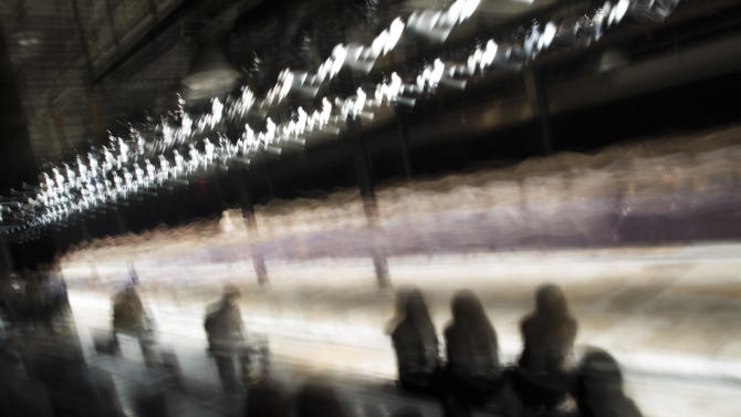 In this photo made with a long exposure, models rehearse on the runway before the Theyskens' Theory Fall 2013 fashion show during Fashion Week, Monday, Feb. 11, 2013, in New York. (AP Photo/John Minchillo)