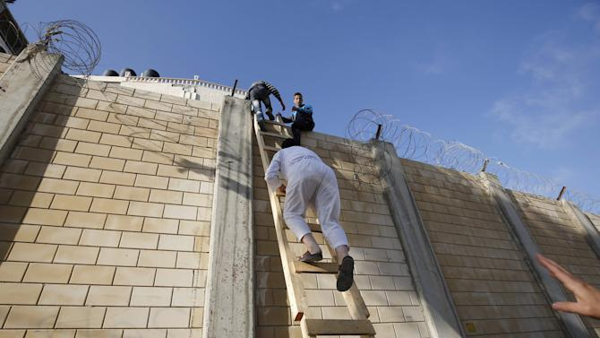 Palestinians climb over a section of the controversial Israeli barrier as they try to make their way to attend the third Friday prayer of Ramadan in Jerusalem's al-Aqsa mosque, in the village of Al-Ram, near Ramallah