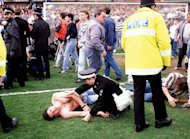 Police rescue soccer fans at Hillsborough stadium April, 15, 1989, after 96 fans were crushed to death and hundreds injured when support railings collapsed during a match between Liverpool and Nottingham Forest. Families of those killed in the Hillsborough football stadium disaster will Monday demand new inquests