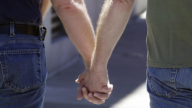 Two men hold hands while walking on Castro Street in San Francisco, Thursday, June 27, 2013. The Supreme Court issued rulings Wednesday that struck down a provision of a federal law that denies federal benefits to married gay couples and also cleared the way for state laws that recognize marriage equality. (AP Photo/Jeff Chiu)