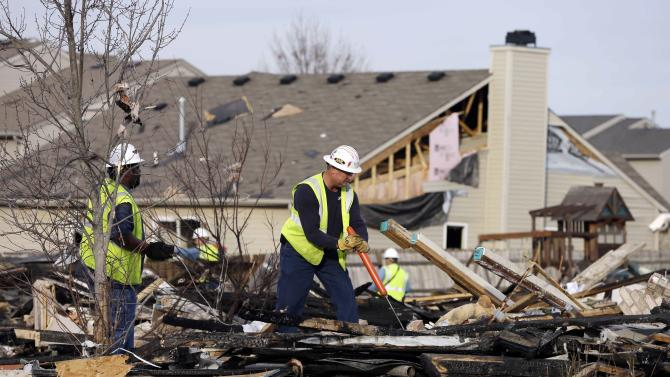 Citizens Energy Group workers work at the site of a home explosion Sunday, Nov. 11, 2012, in Indianapolis. Nearly three dozen homes were damaged or destroyed, and seven people were taken to a hospital with injuries, authorities said Sunday. The powerful nighttime blast shattered windows, crumpled walls and could be felt at least three miles away. (AP Photo/Darron Cummings)