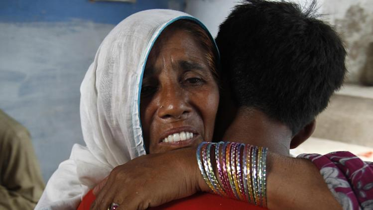 """In this Friday, July 19, 2013, photo, Taj Bibi hugs her lost grandson Zeeshan Ali in Rawalpindi, Pakistan, when they reunite after six years. Bibi told that, """"We wept for him. We looked for him everywhere. We searched for him everywhere. Then, I started consoling my son and I told him that my grandson will come back one day,"""" she said, with one arm wrapped around her grandson. The overwhelmed boy could do little more than cry and say he was happy to be home. (AP Photo/B.K. Bangash)"""