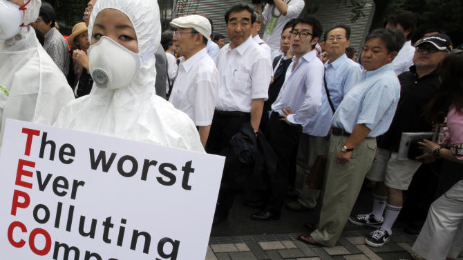 A Greenpeace protester in protective gear holds a banner as shareholders, rear, arrive for the annual shareholders' meeting of Tokyo Electric Power Co. in Tokyo on Tuesday June 28, 2011. Executives at the Japanese utility behind the nuclear power plant sent into meltdown by the March quake apologized to investors who repeatedly interrupted the shareholders' meeting with heckles, yells and questions of outrage. (AP Photo/Itsuo Inouye)