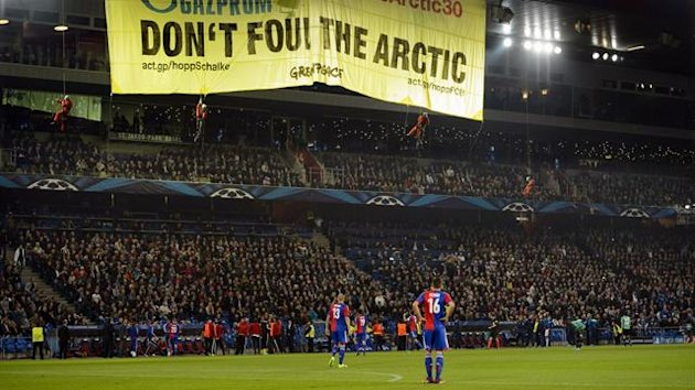 Greenpeace activists display a banner, during the Champions League group E group stage soccer match between Switzerland's FC Basel and Germany's FC Schalke 04 at the St. Jakob-Park stadium in Basel, Switzerland, Tuesday, Oct. 1, 2013. (AP Photo/Keystone,