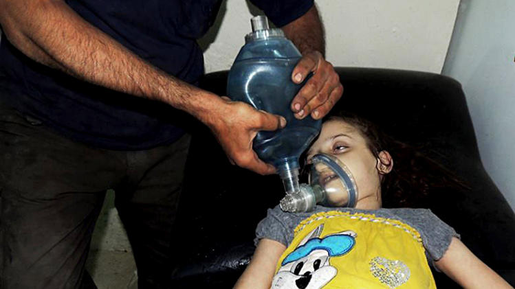 In this Aug. 21, 2013, file citizen journalism image provided by the Local Committee of Arbeen which has been authenticated based on its contents and other AP reporting, a Syrian girl receives treatment at a makeshift hospital in Arbeen town, Damascus, Syria. The early-morning barrage against rebel-held areas around the the Syrian capital Damascus immediately seemed different: The rockets made a strange, whistling noise. Seconds after one hit near his home, Qusai Zakarya says he couldn't breathe, and he desperately punched himself in the chest to get air. Hundreds of suffocating, twitching victims flooded into hospitals. Others were later found dead in their homes, towels still on their faces from their last moments trying to protect themselves from gas. Doctors and survivors recount scenes of horror from the alleged chemical attack a week ago. (AP Photo/Local Committee of Arbeen, File)