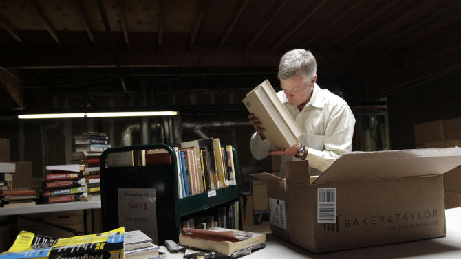 """In this July 21, 2011 photo, Mark, who did not give his last name, unpacks boxes of books at the Internet Archive's Physical Archive warehouse in Richmond, Calif. Saving a copy of every Web page ever posted sounds like an ambitious life's work, but Brewster Khale has decided digital isn't enough. The founder of the Internet Archive wants to expand his effort to provide """"universal access to all knowledge"""" by preserving a physical copy of every book ever written. (AP Photo/Jeff Chiu)"""