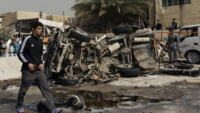 An Iraqi walks past the scene of a car bomb attack in the Ameen neighborhood of eastern Baghdad, Iraq, Sunday, Feb. 17, 2013. A series of car bombs exploded within minutes of each other as Iraqis were out shopping in and around Baghdad on Sunday, killing and wounding scores of people, police said. (AP Photo/ Khalid Mohammed)