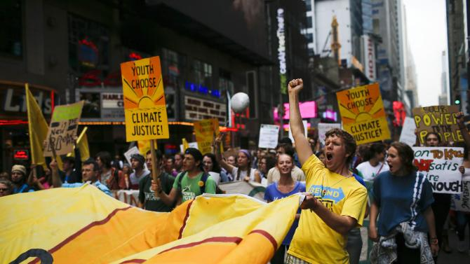 People shouts slogans while they march through Times Square against climate change in New York