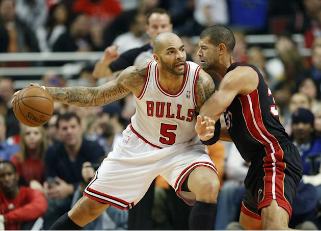Chicago Bulls forward Carlos Boozer, left, looks for an opening against Miami Heat forward Shane Battier, right, during the first half of an NBA basketball game in Chicago, Thursday, Dec. 5, 2013