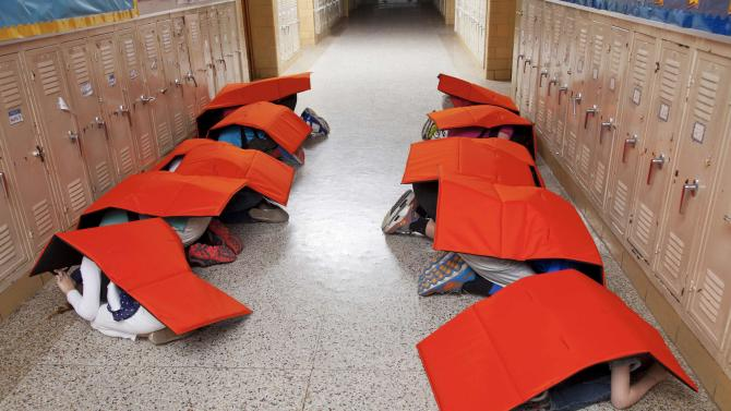 """ProTechtusa handout illustration picture shows children shielding themselves using the """"Body Guard"""" blanket"""