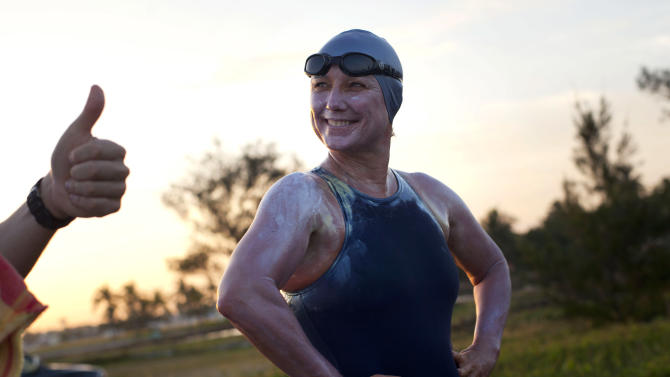 British-Australian swimmer Penny Palfrey smiles as she is flashed a thumbs up at the start of her bid to complete a record swim from Cuba to Florida, in Havana, Cuba, Friday, June 29, 2012. Palfrey aims to be the first woman to swim the Straits of Florida without the aid of a shark cage. Instead she's relying on equipment that surrounds her with an electrical field to deter the predators. (AP Photo/Ramon Espinosa)