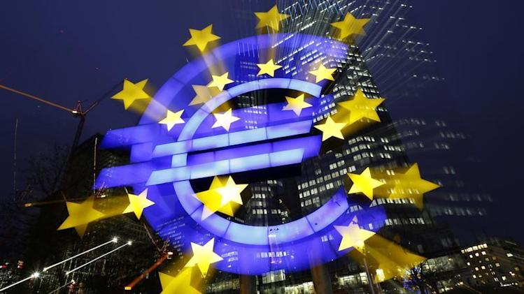 An illuminated euro sign is seen in front of the headquarters of the European Central Bank in the late evening in Frankfurt