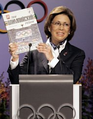 Former Russian world figure skating champion Irina Rodnina holds up a pamphet at Moscow's presentation to the International Olympic Committee in Singapore in July 2005