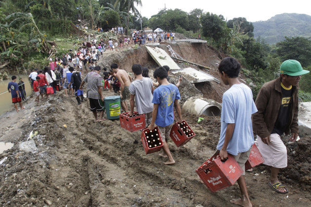 People carry their merchandise on a muddy part of the collapsed road in suburban Antipolo City, east of Manila, Philippines, Thursday, Aug. 9, 2012. The road collapsed at the height of the rain yester