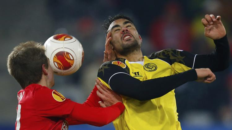 Freiburg's Immanuel Hoehn and Sevilla's Vicente Iborra fight for the ball during their Europa League soccer match in Freiburg
