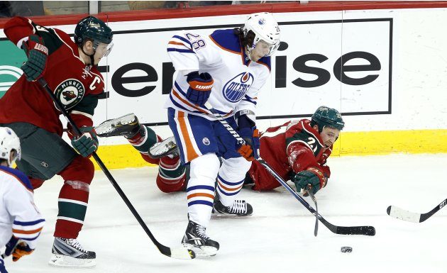 Minnesota Wild defenseman Kyle Brodziak cannot keep the puck from Edmonton Oilers left wing Ryan Jones in St. Paul