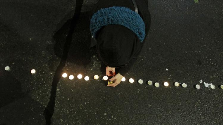A woman lights candles for the victims of the 1989 bloody anti-communist Romanian revolution, in Bucharest