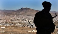 A Yemeni soldier stands on a hill overlooking Saana. At least 60 people were killed on Monday when Al-Qaeda militants raided a barracks, the latest in a spate of attacks by the extremist network which has boosted its presence in Yemen's lawless south and east
