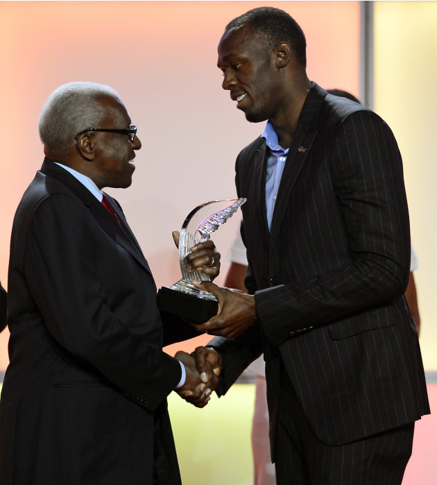 President  of the IAAF Lamine Diack, left, presents the Athlete of the Year Award to Jamaican athlete Usain Bolt, during an event marking the centenary of the IAAF (International Association of Athlet