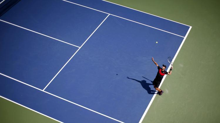 Feliciano Lopez of Spain serves to Ivan Dodig of Croatia during their match at the 2014 U.S. Open tennis tournament in New York