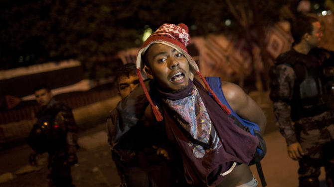 A supporter of indigenous people is grabbed by riot police outside the old Indian Museum in Rio de Janeiro, Friday, March 22, 2013. The clash Friday is a bid to expel the group, some of whom have been squatting in the crumbling complex for years. The Indian museum has been at the center of a drawn-out legal battle between the several dozen Indians who've been living there for years and state and local authorities. Officials initially wanted to raze the complex as part of renovations ahead of Brazil's 2014 World Cup. (AP Photo/Felipe Dana)