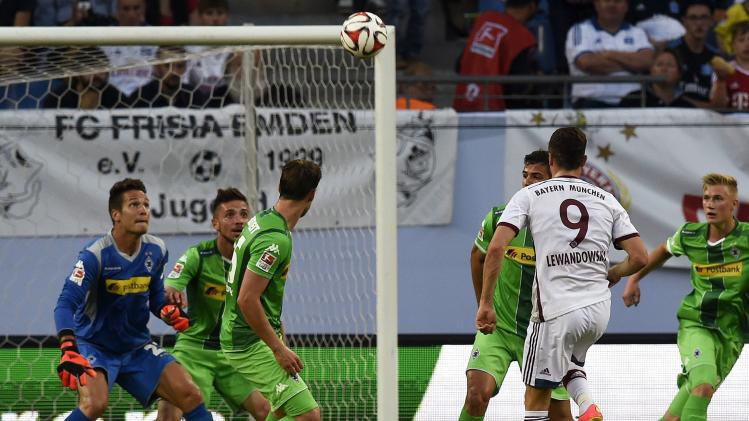 Bayern Munich's Robert Lewandowski scores a goal against Borussia Moenchengladbach's goalkeeper Janis Blaswich during their German Telekom Cup soccer match in Hamburg
