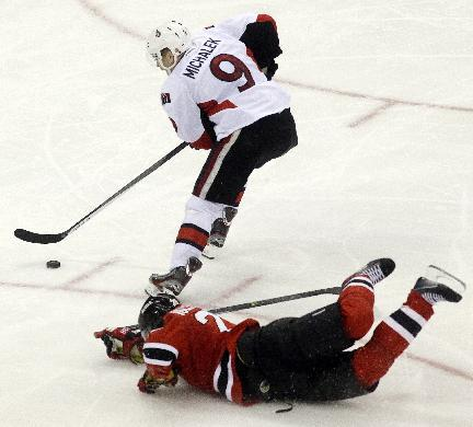 Ottawa Senators left wing Milan Michalek (9), of the Czech Republic, skates past New Jersey Devils defenseman Anton Volchenkov, of Russia, before scoring a goal during the third period of an NHL hocke