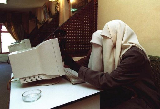 Two veiled Jordanian university students surf the web at an internet cafe in Irbid on 23 January 2001. Jordanian journalists voiced alarm on Wednesday over newly approved amendments to the press and publication law, warning that they threatened freedom of expression particularly in the online media